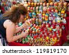 MOSCOW - JULY 26: Unidentified tourists choose a Matryoshka at the gift shop on July 26, 2012 in Moscow on Red Square. Nesting dolls are the most popular souvenirs from Russia - stock photo