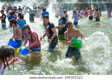 "MOSCOW - JULY 14: Young people shooting and throwing water at each other during flash mob ""Water Battle"" in Peoples Friendship Fountain in VDNKH on July 14, 2012 in Moscow, Russia"
