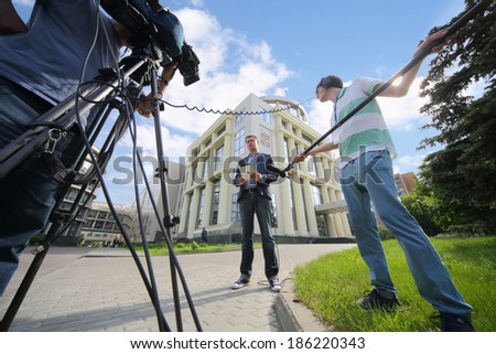 MOSCOW - JUN 11: Journalists near building of the Moscow City Court with russian flag on June 11, 2013 in Moscow, Russia.