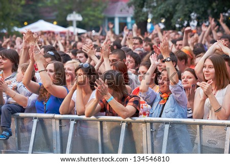 MOSCOW - JUN 23: Music fans applaud at concert of Chaif rock-band during VII traditional festival of live sound Music of Summer in Hermitage Garden, Jun 23, 2012, Moscow, Russia. - stock photo