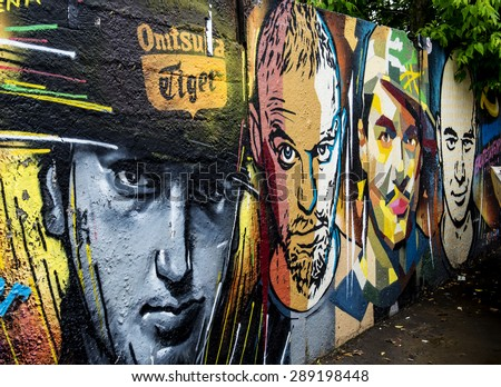 MOSCOW - JUNE 21, 2015: Graffiti on a urban wall (near B. Novodmitrovskaya street). Men's faces.  - stock photo