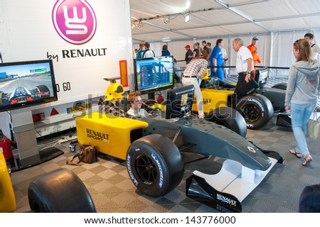 MOSCOW - JUNE 23: People attend the Formula 1 simulator at World Series by Renault in Moscow Raceway on June 23, 2013 in Moscow - stock photo