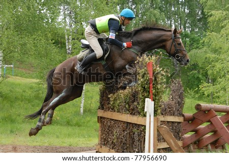 MOSCOW - JUNE 06: Vakin Maksim on Harlej-Devidson (Trakehnen) jumps through an obstacle on a Russian Cross-Country Championship, CIC 2* on June 06, 2009 in Moscow.