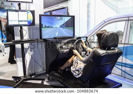 MOSCOW-June 1: Woman driving training simulator at the international exhibition of navigation equipment and software Navitech on June 1, 2011 in Moscow - stock photo