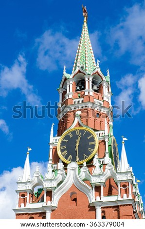 Moscow Kremlin, Red Square. Spasskaya Tower and Kremlin clock decorated by the red ruby star on the top of it. Blue sky background. UNESCO World Heritage Site. Moscow, Russia. - stock photo
