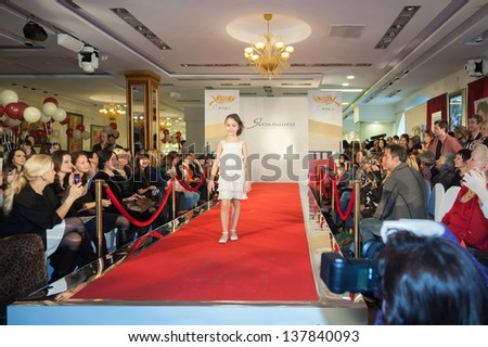 MOSCOW - MAR 18: The girl on the runway and spectators at a fashion show in a childrens store Jakimanka on March 18, 2012 in Moscow, Russia.