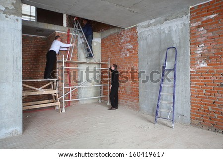 MOSCOW - MAR 14: Three men in room with brick wall use stepladder in DS Exploitation at House in Sokolniki on March 14, 2013 in Moscow, Russia.