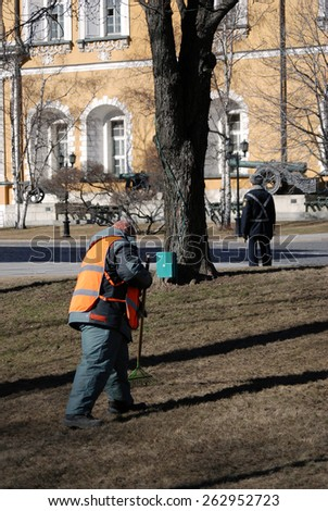MOSCOW - MARCH 17, 2015: A worker grabs old leaves from the ground. Spring cleaning in Moscow Kremlin, a popular touristic landmark. UNESCO World Heritage Site.
