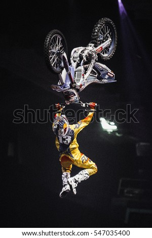 MOSCOW - 14 MARCH,2015: Extreme sport competition show Proryv.Freestyle motocross athlete jump high from big air ramp performing dangerous superman backflip trick on bike