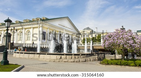 "MOSCOW - MAY 15, 2014: exhibition hall ""Manezh"" in Alexandrovskiy garden on Manezhnaya square, has been built in 1817 year and lilac in blossom in spring in Alexandrvosky garden. - stock photo"