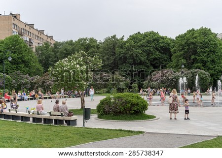 MOSCOW - MAY 29: Flowering spring lilac (syringa) garden with vintage street lamps, fountain and people on May 29, 2015 in Moscow.