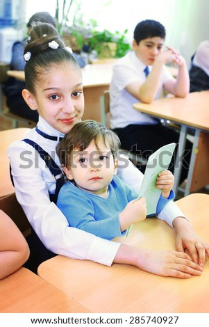 MOSCOW, MAY 26, 2015: Graduation in the primary school in Moscow, May 26. Graduating girl with her little brother  in the classroom gets diploma and then go to the middle school.