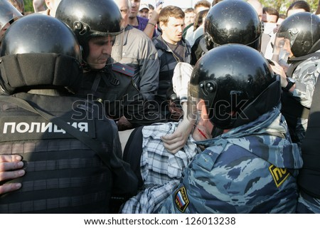 MOSCOW - MAY 6: Injured person is carried away by police during the demonstration against newly elected president Vladimir Putin on May 6, 2012 in Moscow, Russia. - stock photo