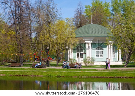 MOSCOW - MAY 07: People and the wooden pavilion on the shore of the pond in Catherine Park on May 7, 2015 in Moscow. Catherine Park is located in Moscow's Meshchansky District. - stock photo