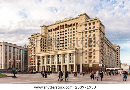 MOSCOW - MAY 16: People walking near  the Four Seasons Hotel Moscow on May 16, 2014 in Moscow. The  Hotel Moscow is a modern luxury hotel with a facade that replicates the historic Hotel Moskva. - stock photo