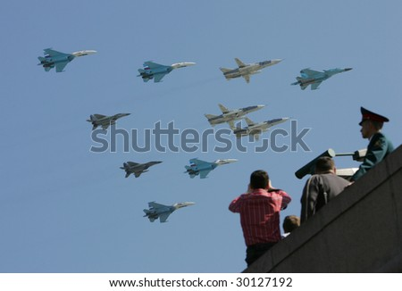 MOSCOW - MAY 9: People watch a squadron of Russian fighter jets fly in formation over Red Square during Victory Day parade May 9, 2009 in Moscow, Russia.