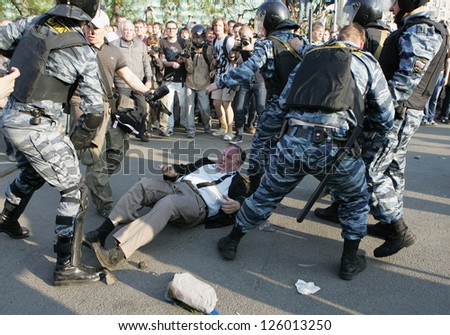 MOSCOW - MAY 6: Police attack journalists during the demonstration against newly elected president Vladimir Putin on May 6, 2012 in Moscow, Russia. - stock photo