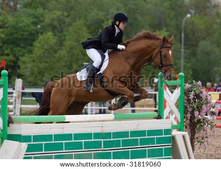 MOSCOW - MAY 16: Rider on his horse  jumps over the barrier in CSKA Summer Showjumping Cup event May 16, 2009 in Moscow, Russia - stock photo