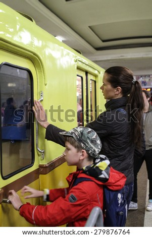 MOSCOW - MAY 5, 2015: Unidentified people to touch an old subway car at the exhibition of retro-cars dedicated to the 80th anniversary of the Moscow Metro. Public-event - stock photo