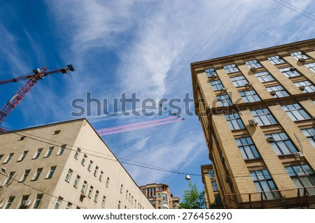 MOSCOW-MAY 9, 2015: Victory parade dedicated to the 70th anniversary of the Soviet victory over Germany. Demonstration aircraft flying over the rooftops of the city and the heads of the people, the - stock photo