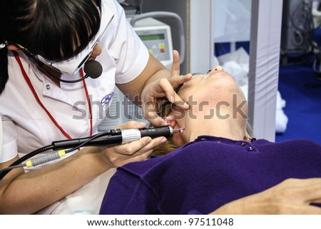 MOSCOW - OCTOBER 26: Beautician performs a laser procedure at the international exhibition of professional cosmetics and beauty salon equipment INTERCHARM on October 26, 2011 in Moscow - stock photo