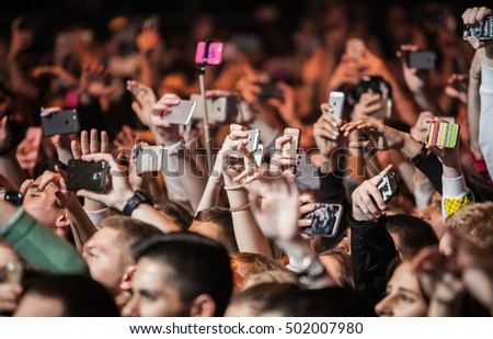 MOSCOW - 20 OCTOBER,2016 : Crowded dancefloor in nightclub.Big live music show in night club.Music fans hands with smart phone camera film concert.Crowd with selfie sticks,many mobile phones filming
