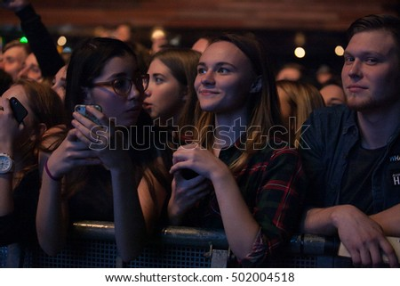 MOSCOW-2 OCTOBER,2016: Happy young girls having fun on concert in night club.Pretty young girls enjoy music concert in the club.Music hall entertainment show.Concert crowd in music hall.Rock concert