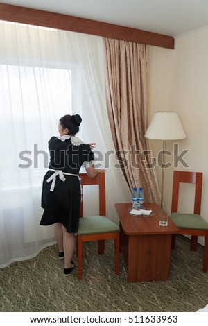 MOSCOW - OCTOBER 31: Maid girl, dressed in black, making cleaning procedure at room in Izmaylovo hotel on October 31, 2016 in Moscow. Izmailovo is four-building hotel in Izmaylovo District of Moscow.