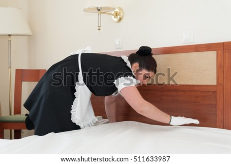 MOSCOW - OCTOBER 31: Maid girl, dressed in black, putting blanket on bed at room in Izmaylovo hotel on October 31, 2016 in Moscow. Izmailovo is four-building hotel in Izmaylovo District of Moscow.