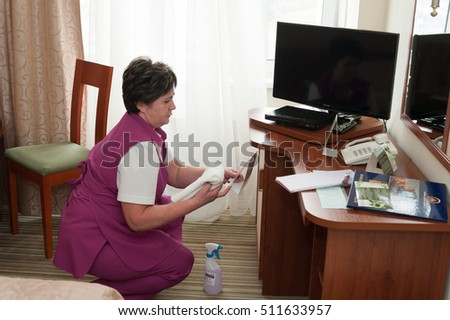 MOSCOW - OCTOBER 31: Maid woman, dressed in purple, making cleaning procedure at room in Izmaylovo hotel on October 31, 2016 in Moscow. Izmailovo is four-building hotel in Izmaylovo District of Moscow