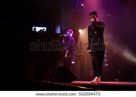MOSCOW - 20 OCTOBER,2016 : Rap singer sing on stage of night club.Hip hop music performer singing in microphone on scene.Rapper in bright concert lighting.