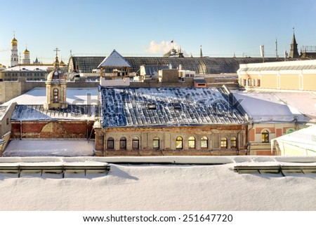 Moscow old roofs. Unusual view from the roofs of Ilyinka street on the GUM roof and the Kremlin towers and cathedrals far away on the back stage. Shot made In a snowy winter day. - stock photo