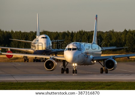 Moscow region, Domodedovo, Russia - August 18, 2013: Airbus A320 Ural airlines VQ-BFV taxiing for take off and Boeing 747-400 Transaero airlines behind of him at Domodedovo international airport - stock photo