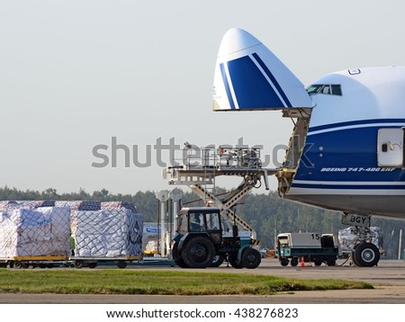MOSCOW REGION, RUSSIA - JULY, 2011: Cargo loading to AirBridgeCargo Boeing 747-400ERF cargo aircraft open nose close up with loader and tractor on foreground