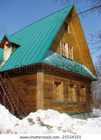 Moscow. Reserve in Kolomna. A winter sunny day. Russian log hut, wooden walls a green roof.