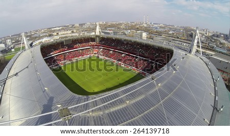 MOSCOW, RUSSIA - APR 28, 2014: People watch football match in Locomotive sports stadium at evening. Aerial view - stock photo