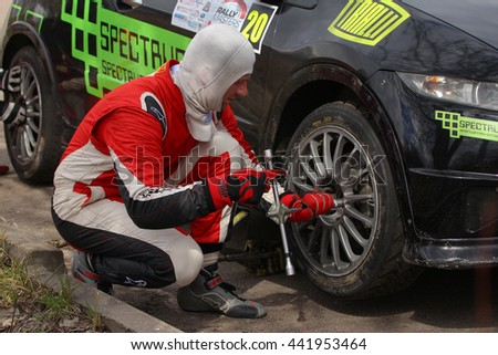 Moscow, Russia - Apr 18, 2015: Unidentified driver changing car wheel during the Rally Masters Show 2015 at the Krylatskoye District. - stock photo