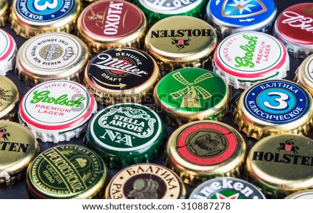 Moscow, Russia - April 28, 2015: Background of beer bottle caps, a mix of various global brands: Grolsch, Bud, Bavaria, Miller, etc. - stock photo