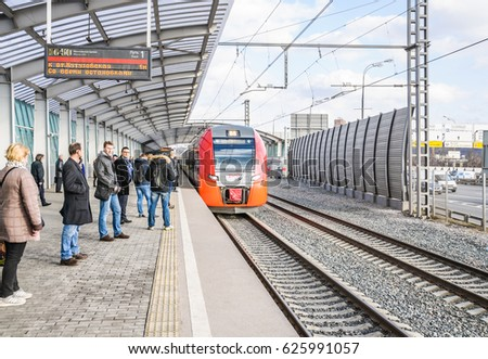 "Moscow, Russia - April 5, 2017: Station ""luzhniki"" of Moscow Central Circle railway. The Lastochka train is approaching. Passengers standing on the platform"