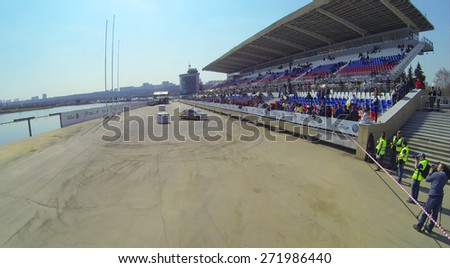 MOSCOW, RUSSIA - APRIL 19, 2014: Tribunes with the people watching the Rally Masters Show on the shore of the Grebnoy canal, aerial view - stock photo