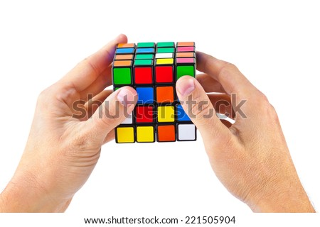 MOSCOW, RUSSIA - August 31, 2014: Hands and Rubik's cube puzzle isolated on the white background. Cube was invented by a Hungarian architect Erno Rubik in 1974. - stock photo