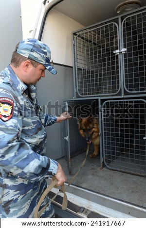 MOSCOW, RUSSIA - AUGUST 8, 2013: Police officers patrol the streets with dogs. Patrol and inspection service of the police provides public safety in the capital.