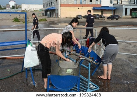 MOSCOW, RUSSIA - AUGUST 5, 2013:  Temporary camp for displaced persons contains illegal migrants from Asian countries, discovered during police raids, pending deportation to their homeland.