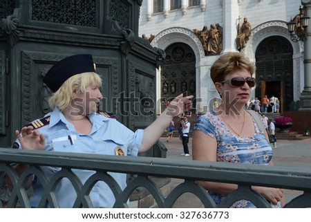 MOSCOW, RUSSIA - AUGUST 13, 2013:The policewoman indicates the direction of the tourist. Employees of patrol police control the territory at the Cathedral of Christ the Savior.