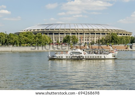 Moscow, Russia - August 10, 2017: View of riverside of Moscow river and floating passenger boat on Luzhniki sport arena background