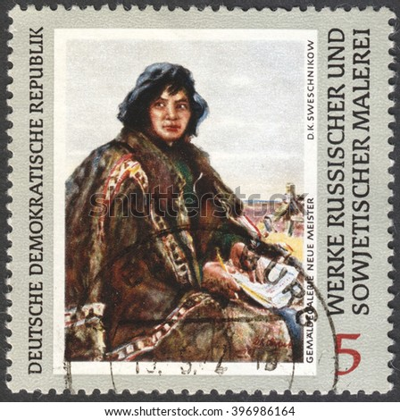 """MOSCOW, RUSSIA - CIRCA FEBRUARY, 2016: a stamp printed in DDR shows a painting """"Siberian Teacher"""" by Svechnikov, the series """"Russian Paintings"""" circa 1969 - stock photo"""