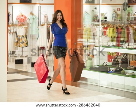 """MOSCOW, RUSSIA - CIRCA MAY 2015: A young girl walks around the store with shopping bags in her hands at Shopping center """"Vegas"""" in Moscow, Russia - stock photo"""