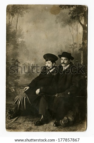 MOSCOW, RUSSIA - CIRCA 1900s: An antique photo shows studio portrait of a two men in overcoats and hats