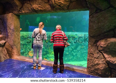 MOSCOW, RUSSIA - DEC 17, 2016: Crocus City Oceanarium. Two tourists watching fish near large aquarium