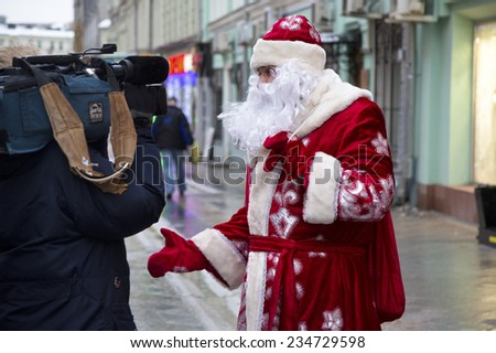 MOSCOW, RUSSIA - DEC 22: Russian Christmas character Ded Moroz (Father Frost) gives an interview to central TV during Ded Moroz flashmob parade on central Moscow street on 22 of December 2013, Russia - stock photo